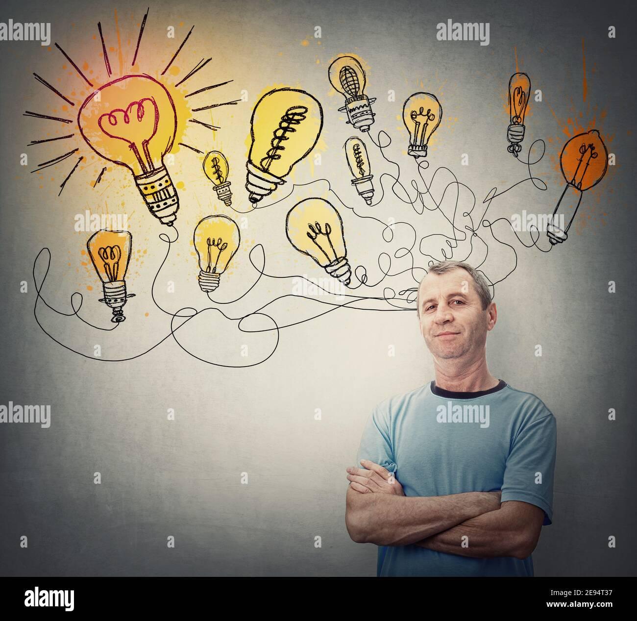 L'uomo creativo di mezza età mantiene le braccia incrociate, guardando fiducioso come molteplici grandi idee. Motivato maschio senior e lampade luminose sopra la sua testa Foto Stock