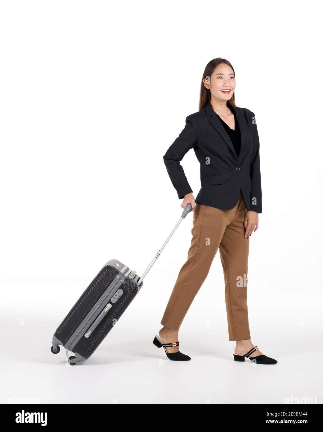 Giovani donne asiatiche in tuta nera sorride mentre cammina trascinando una valigia nera. Ritratto su sfondo bianco con luce da studio. Foto Stock