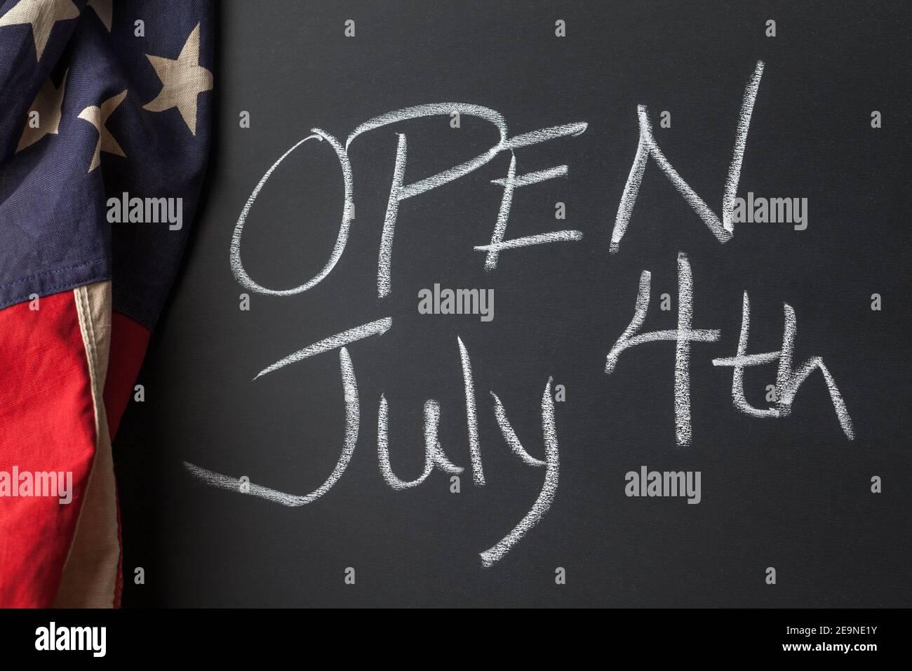 Aperto 4 luglio segno scritto a mano su una lavagna delimitata da Una bandiera americana d'epoca Foto Stock