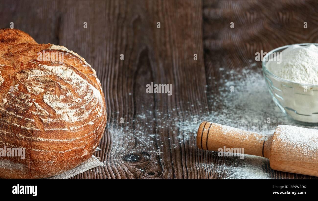 Primo piano di pane tradizionale di pasta acida su uno sfondo rustico di legno. Concetto di cottura tradizionale del pane lievitato. Cibo sano Foto Stock