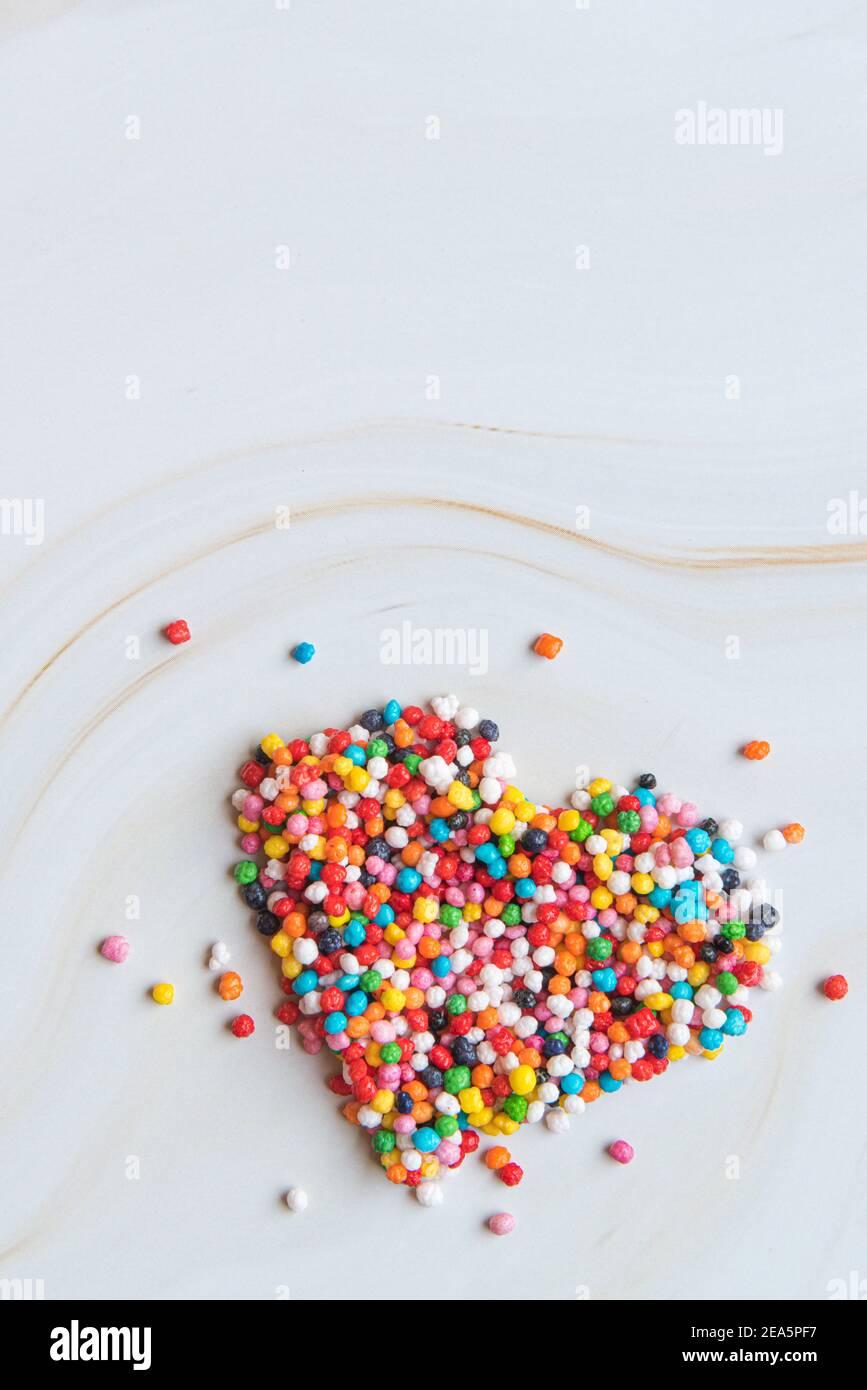 Concetto creativo di amore per le vacanze. Forma a cuore realizzata con piccole caramelle colorate su uno sfondo di marmo bianco. Concetto di San Valentino. Gravidanza concetto di diabete. Vista dall'alto, disposizione piatta. Foto di alta qualità Foto Stock