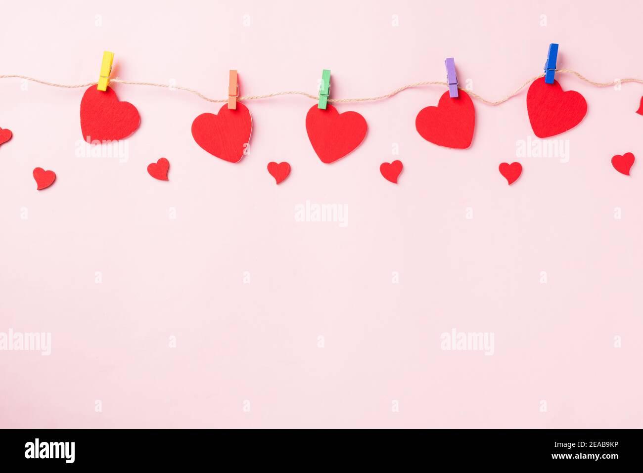 Buon San Valentino sfondo giorno. Cuore rosso decorazione valentine a forma di cuore appeso con graffette sulla corda per amore composizione biglietto di auguri isola Foto Stock