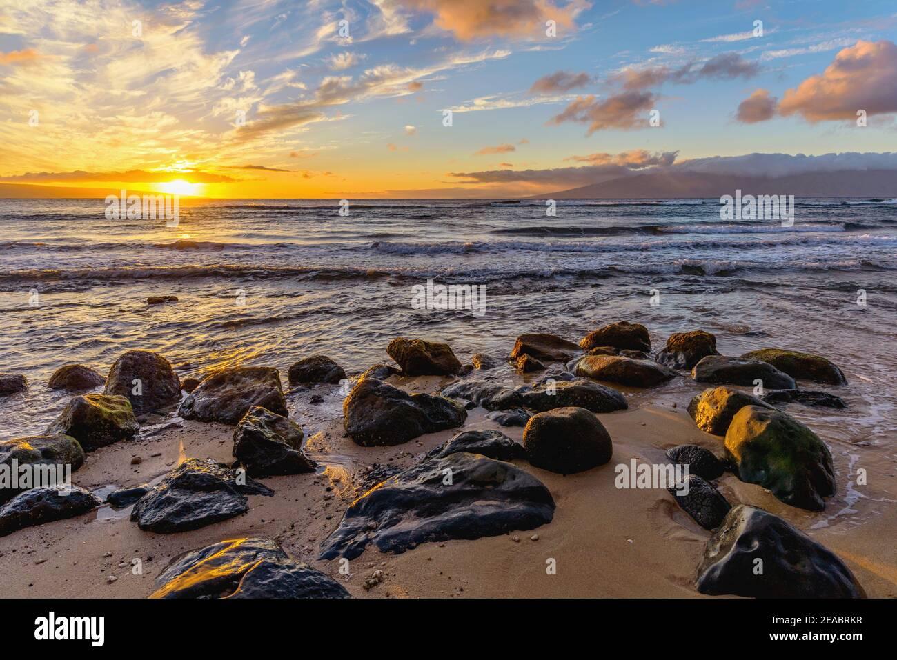 Sunset Rocky Coast - una colorata vista al tramonto di una spiaggia rocciosa sulla costa nord-occidentale di Maui, Hawaii, USA. Foto Stock