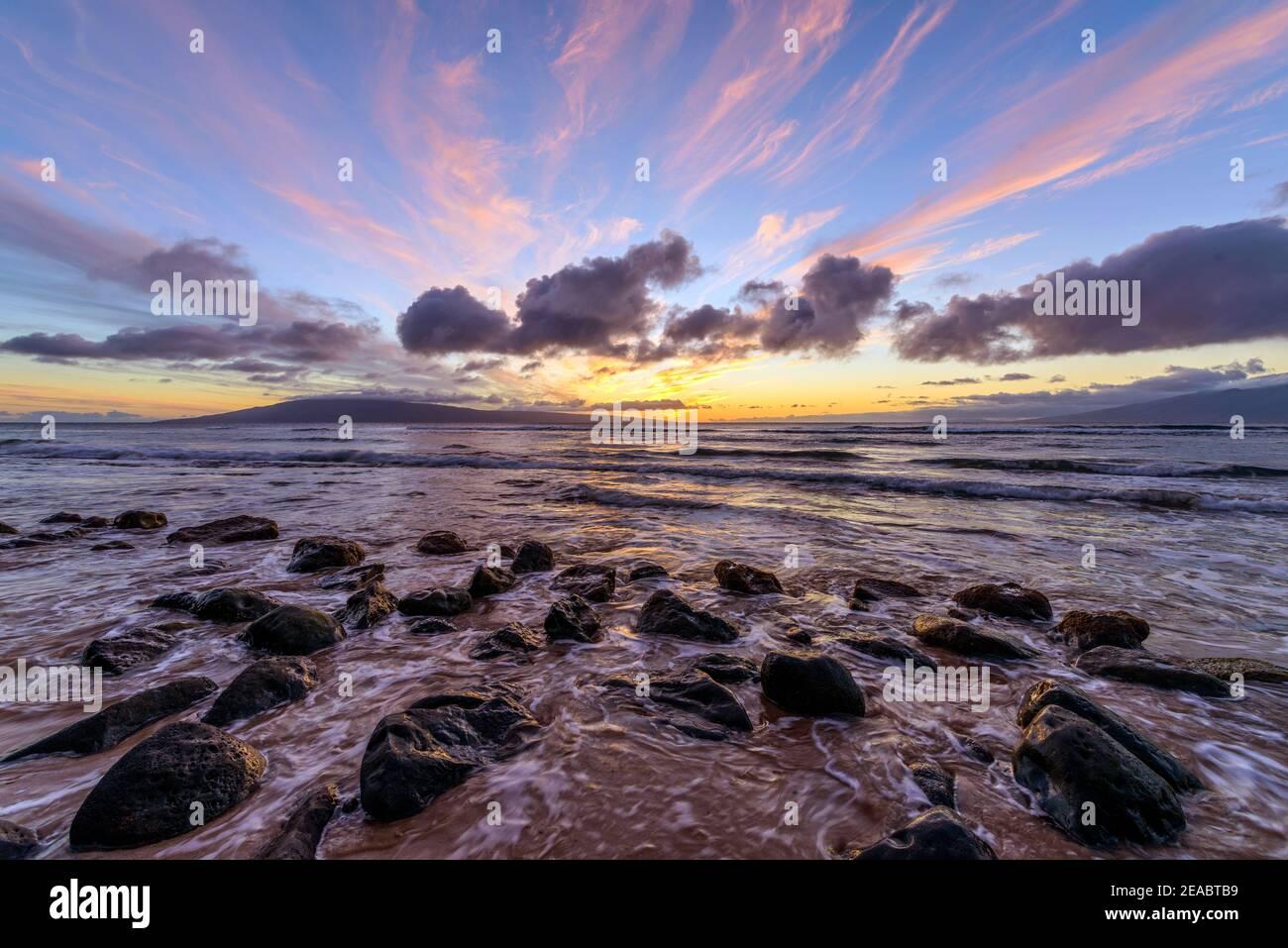 Sunset Rocky Coast - una colorata vista del tramonto su una costa rocciosa della costa nord-occidentale dell'isola di Maui, con l'isola di Lanai all'orizzonte. Maui, Hawaii, Stati Uniti. Foto Stock