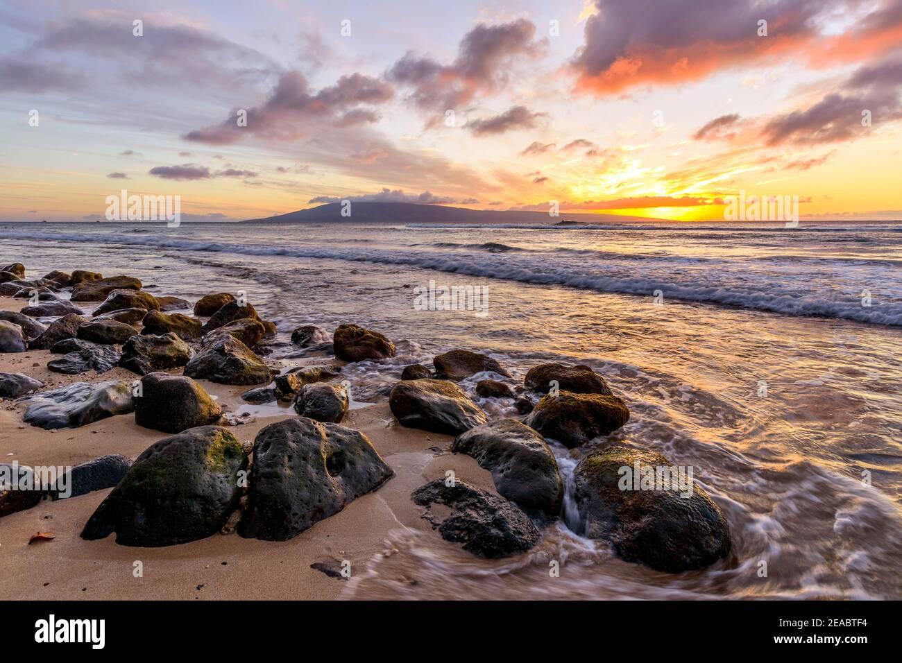 Tramonto tropicale - UN colorato tramonto su una spiaggia rocciosa della costa nord-occidentale dell'isola di Maui, con l'isola di Lanai all'orizzonte. Hawaii, Stati Uniti. Foto Stock