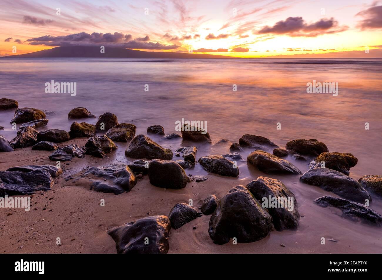 Sunset Island - una vista a lunga esposizione di un colorato tramonto su una spiaggia rocciosa della costa nord-occidentale dell'isola di Maui, Hawaii, USA. Foto Stock