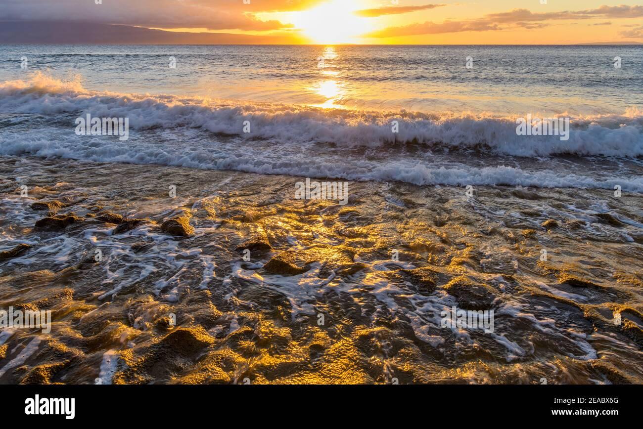 Golden Sunset - luminoso tramonto vista di forti onde che scorrono dentro e fuori dalla costa rocciosa della costa nord-occidentale dell'isola di Maui, Hawaii, USA. Foto Stock