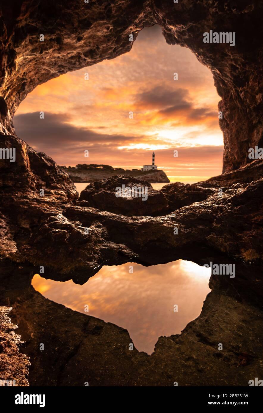Faro di Portocolom, Maiorca, visto dall'interno di una grotta all'alba con una pozza in primo piano che riflette il cielo Foto Stock