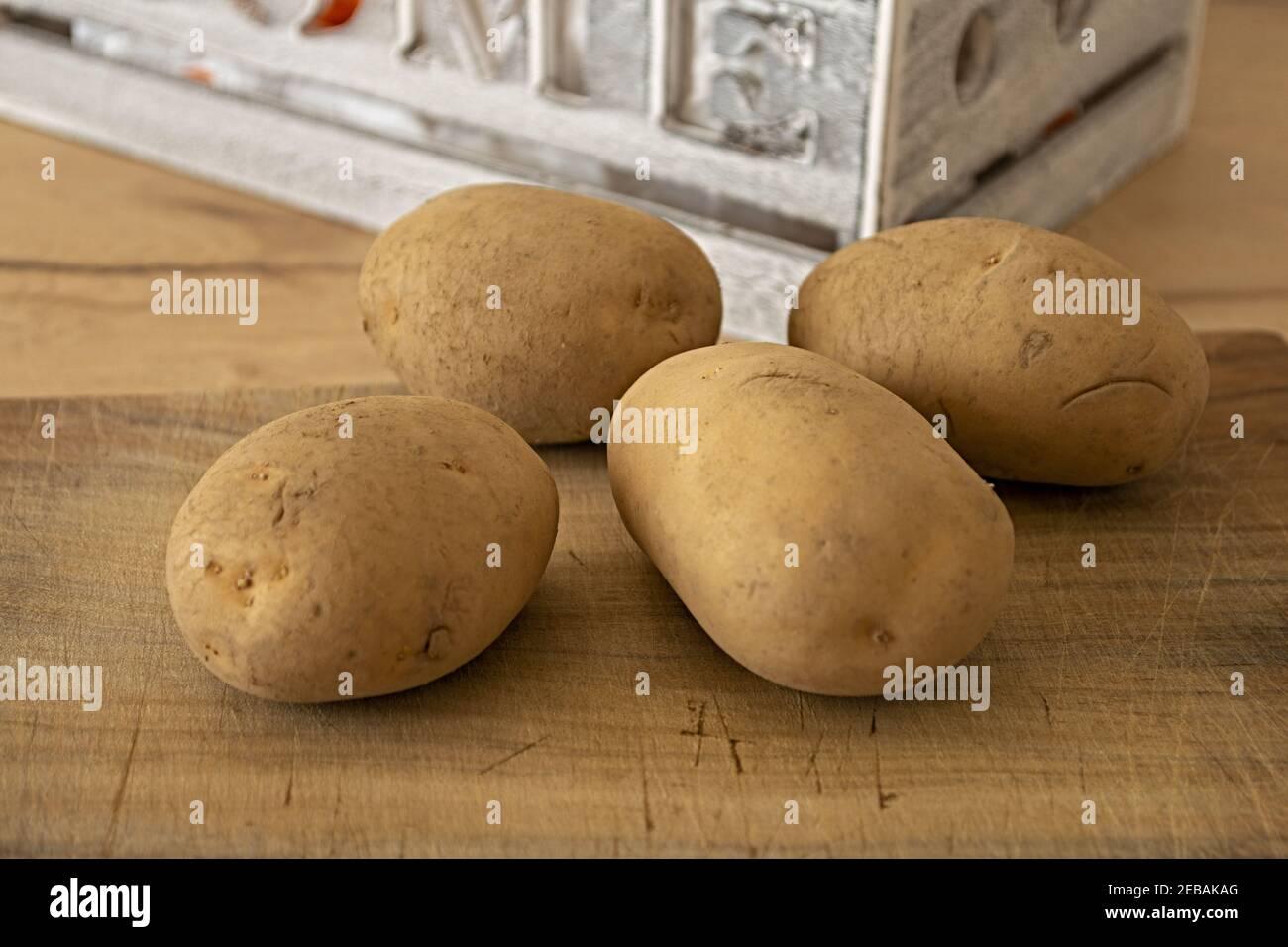 quattro patate sul tagliere altra vista Foto Stock