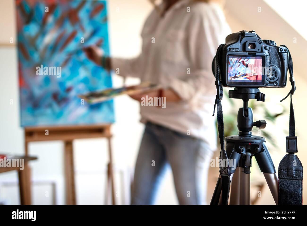 Artista live streaming dal suo studio. Artista femminile che registra il suo video tutorial sulla pittura d'arte. Donna freelance che condivide online il suo lavoro Foto Stock