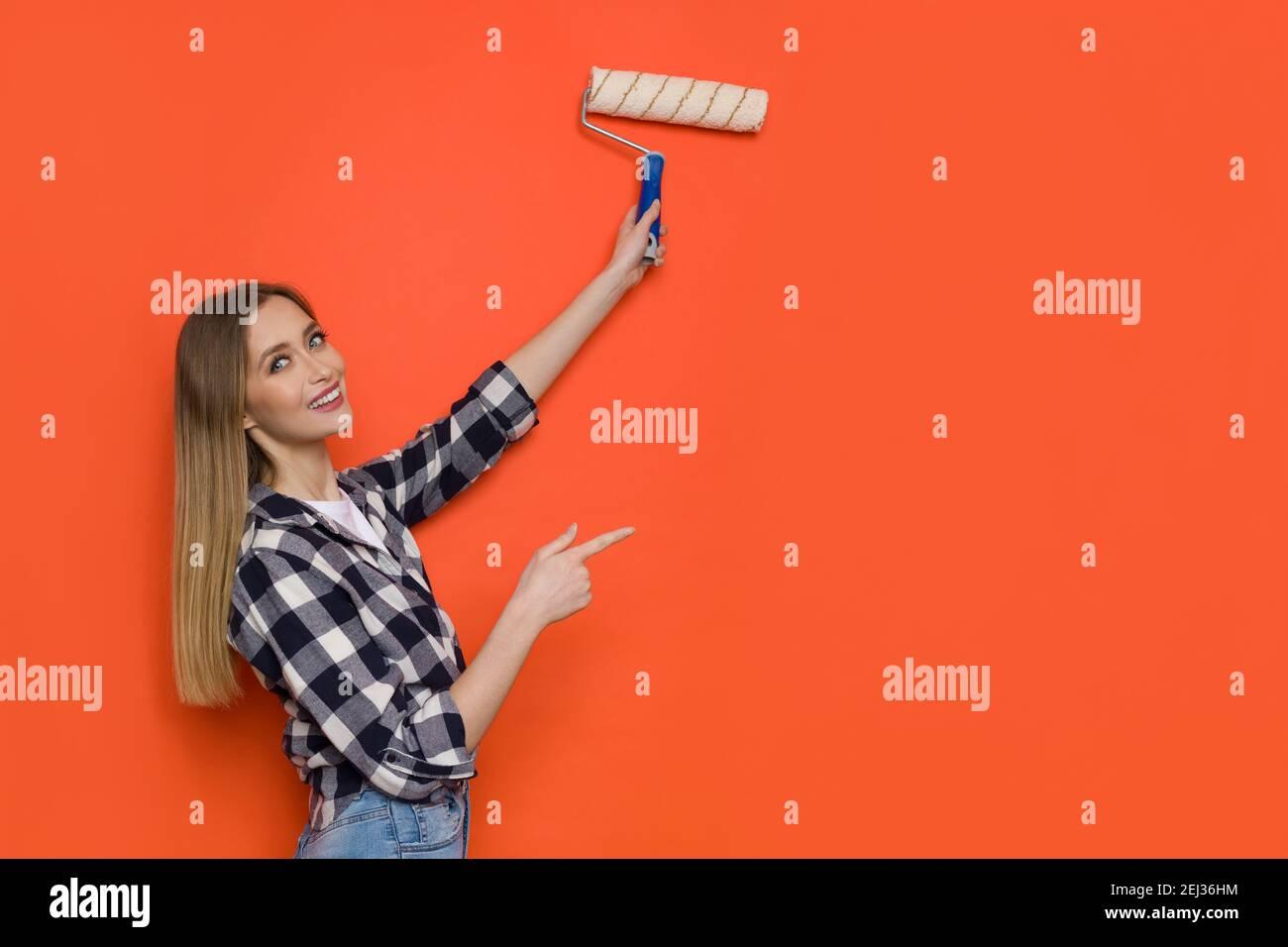 Giovane bionda donna in lumberjack camicia e jeans è pittura arancione parete con rullo pittura, guardando la fotocamera sopra la spalla e puntando. Vita Foto Stock