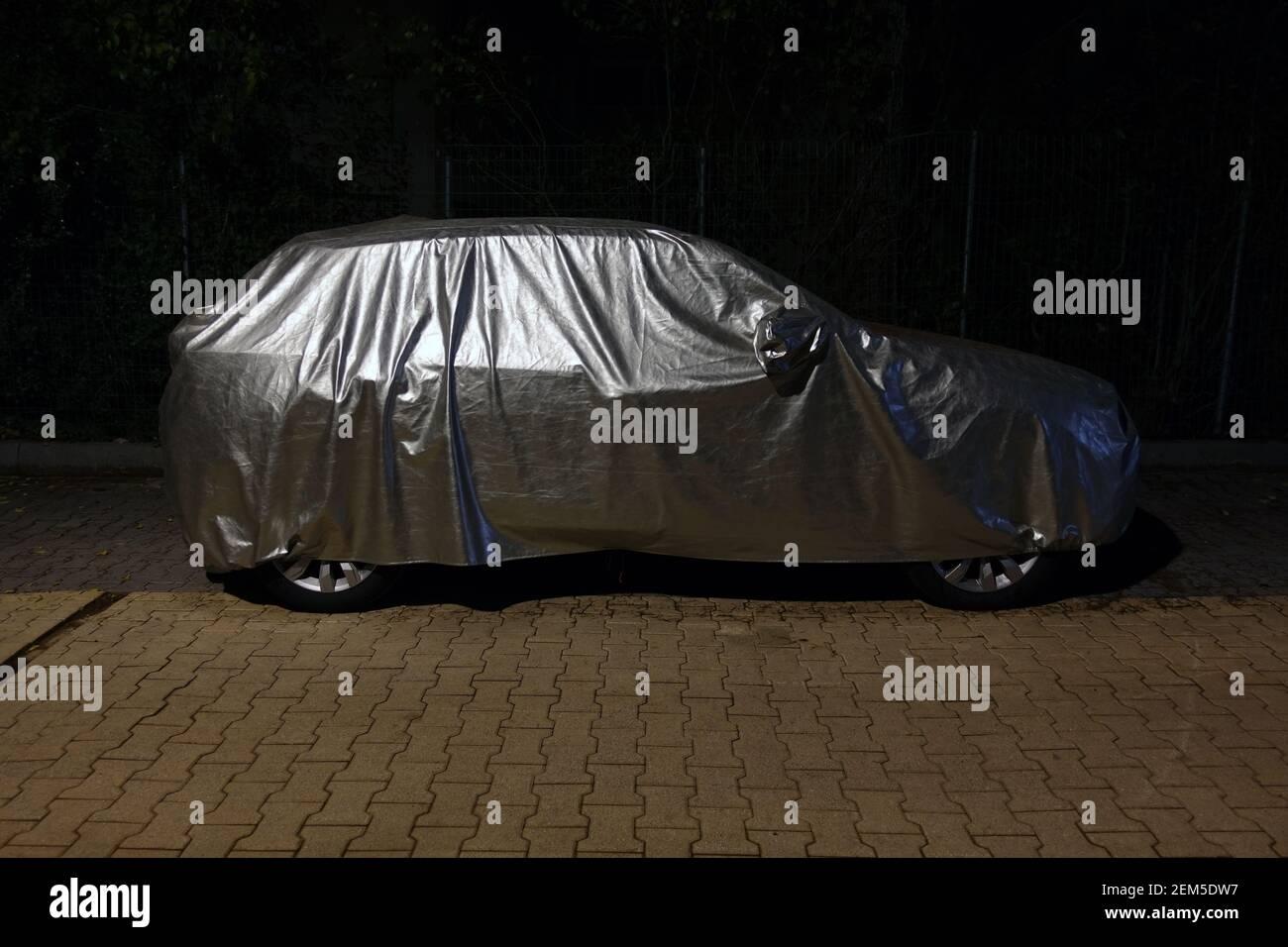 Auto con copertura protettiva in argento di notte. Foto Stock