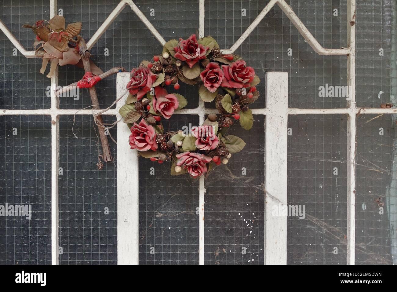 Decorazioni natalizie ornamenti vintage ricoperti di ciottoli sulla porta della casa abbandonata. Corona di plastica rosa fiori rossi cupido con lira e cros di legno Foto Stock