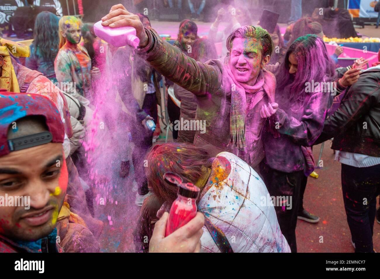 Un uomo è visto lanciare polveri colorate ad una donna. Milioni di persone in tutto il mondo celebrano l'annuale Holi Hangámá Festival, conosciuto anche come Festival dei colori. Per gli indù è una celebrazione dell'arrivo della primavera, del nuovo anno e della vittoria tutto in uno. La più grande popolazione indiana in Europa (al di fuori del Regno Unito) si trova a l'Aia, questa è una delle più grandi d'Europa. Il momento culminante delle celebrazioni Holi è la processione attraverso i quartieri multiculturali Transvaal e Schilderswijk. I partecipanti alla processione gettano polvere colorata su se stessi e a e. Foto Stock