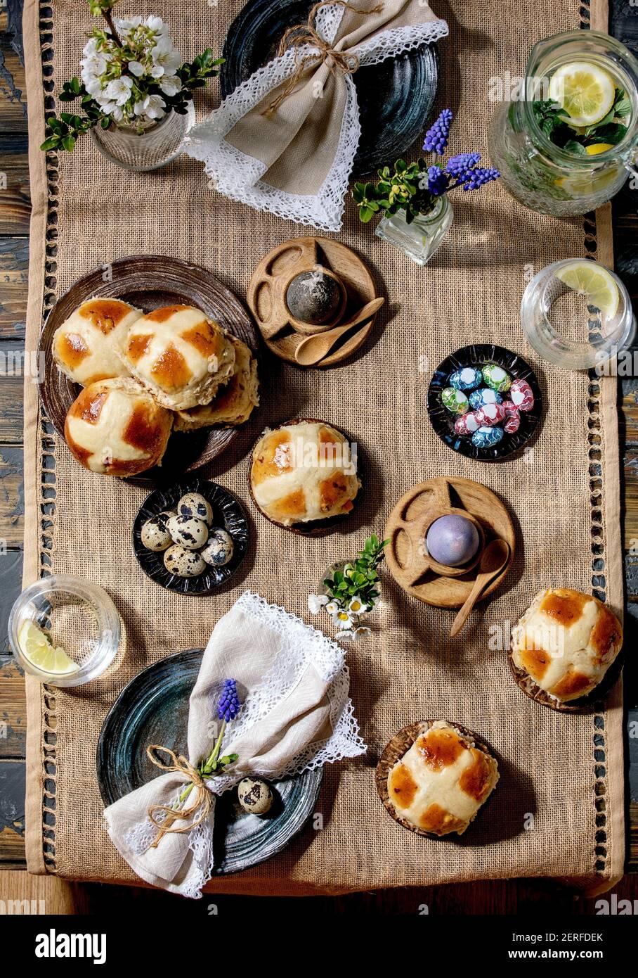 Tavolo pasquale con uova colorate e al cioccolato, mazzi di croce calda, fiori di bouquet, piatto vuoto in ceramica con tovagliolo, bicchiere di bevanda limonata su woo Foto Stock