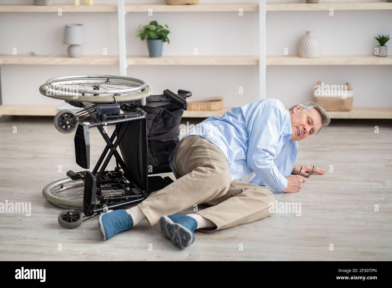 Uomo anziano con disabilità fisica sdraiato sul pavimento dopo la caduta giù dalla sua sedia a rotelle a casa Foto Stock