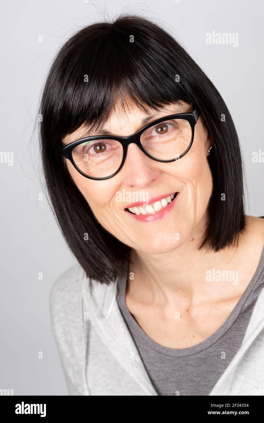 Donna caucasica matura che indossa occhiali sorridenti. Foto Stock