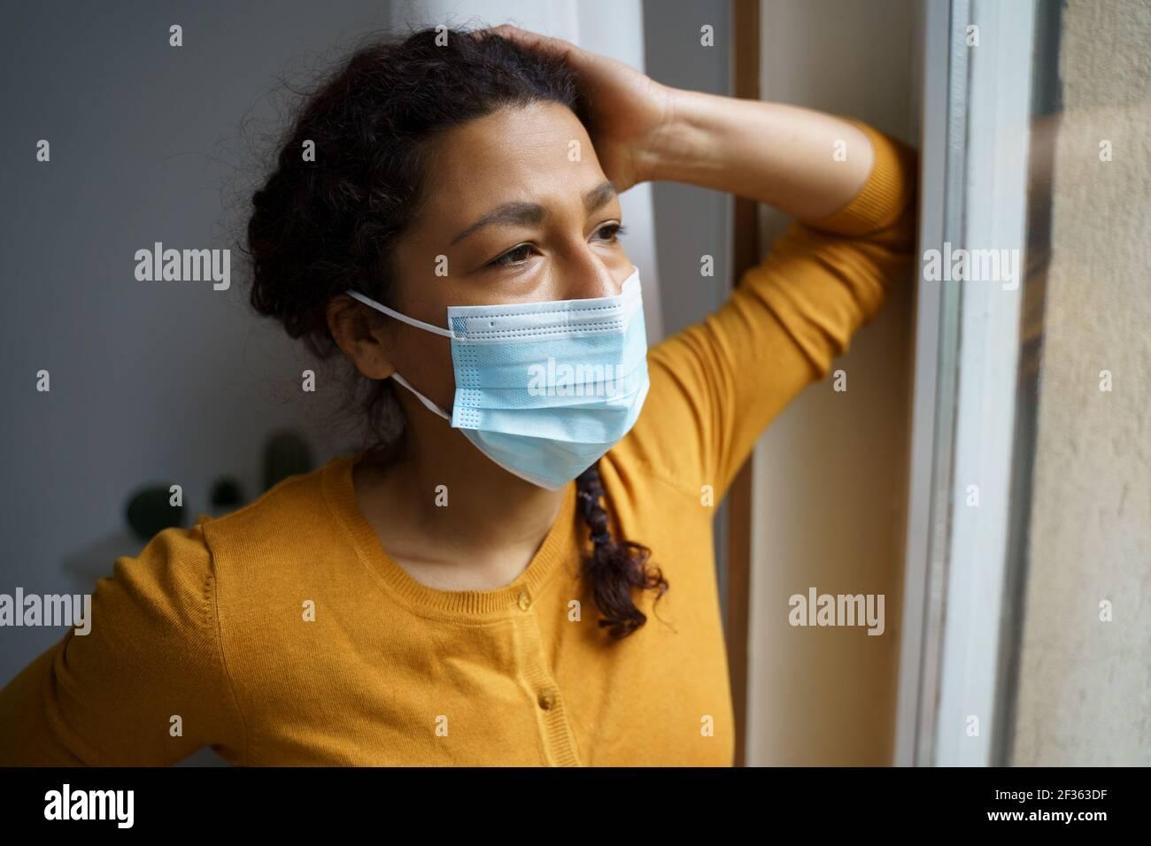 Preoccupata donna nera che guarda fuori dalla finestra Foto Stock