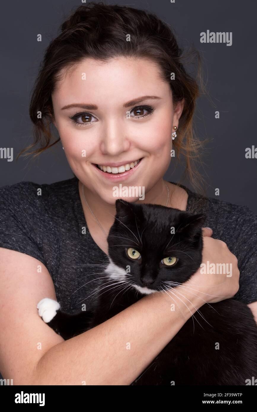 Giovane femmina adulta sorridente con un gatto bianco e nero Foto Stock