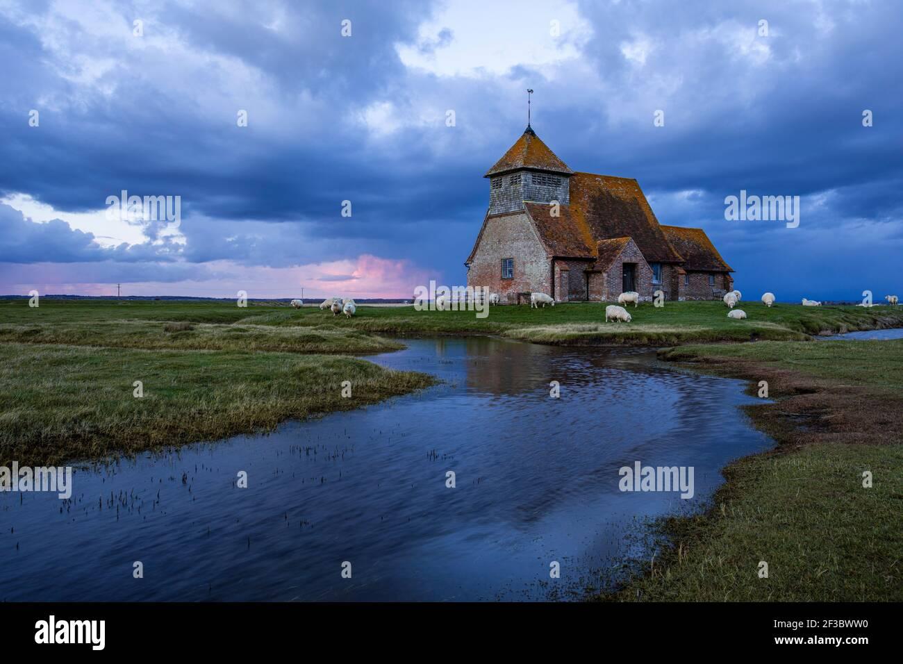 Chiesa di San Thomas Becket vicino a Fairfield sulla Marsh Romney nel Kent, Inghilterra sud-orientale, nubi tempesta che si radunano durante l'ora blu e pascolo delle pecore Foto Stock