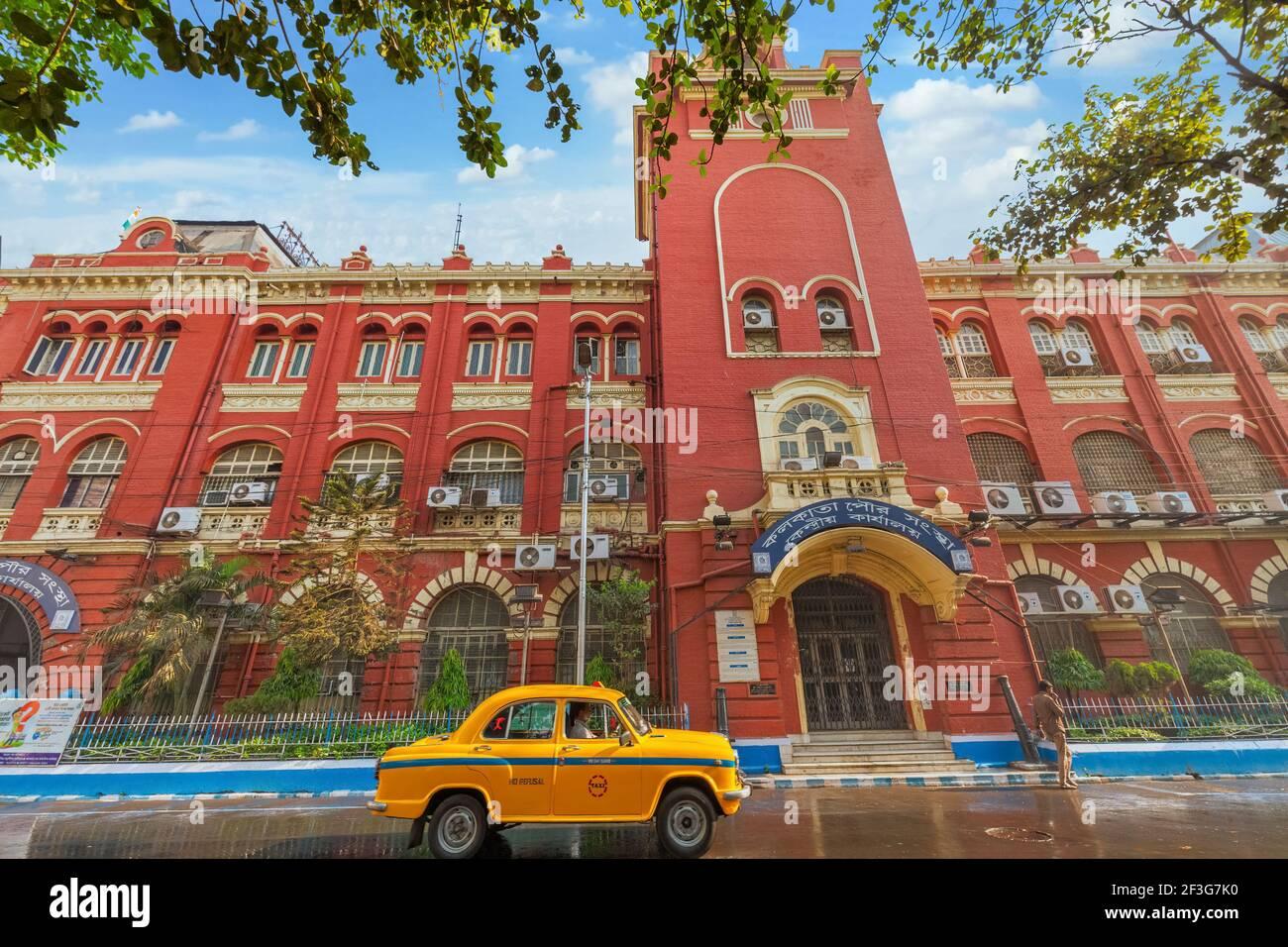 Taxi giallo di fronte al palazzo della Government Municipal Corporation costruito in stile coloniale a Kolkata, India Foto Stock