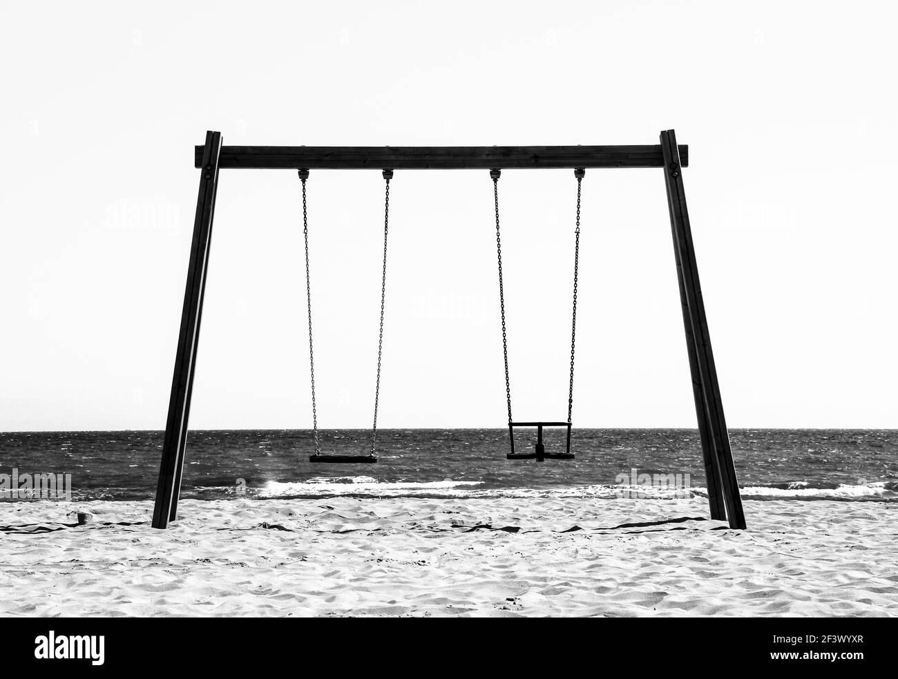 Altalena vuota di legno di fronte al mare al mattino ad Alicante, Spagna. Immagine monocromatica. Foto Stock