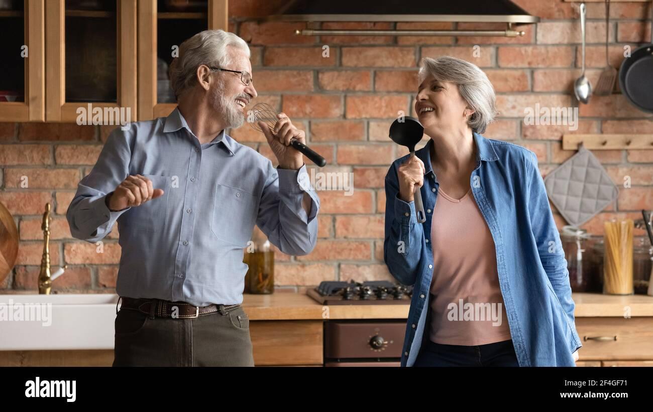 La coppia più anziana si è divertita a cantare canzoni in cucina Foto Stock