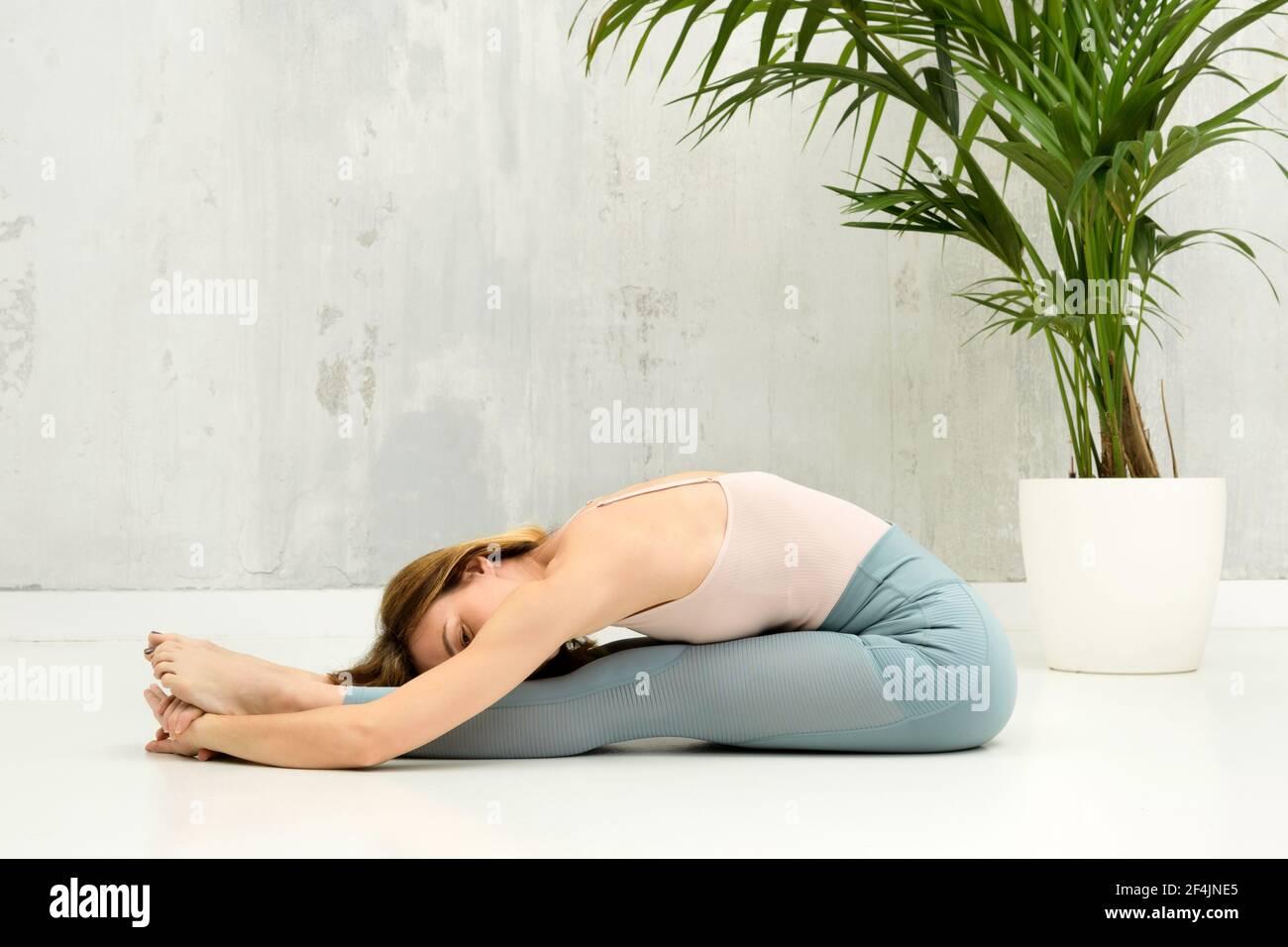 Donna che fa una Pascimottanasana o seduta Forward Bend yoga posa per rilassarsi e allungare le gambe e la colonna vertebrale con copyspace su una parete grigia oltre Foto Stock