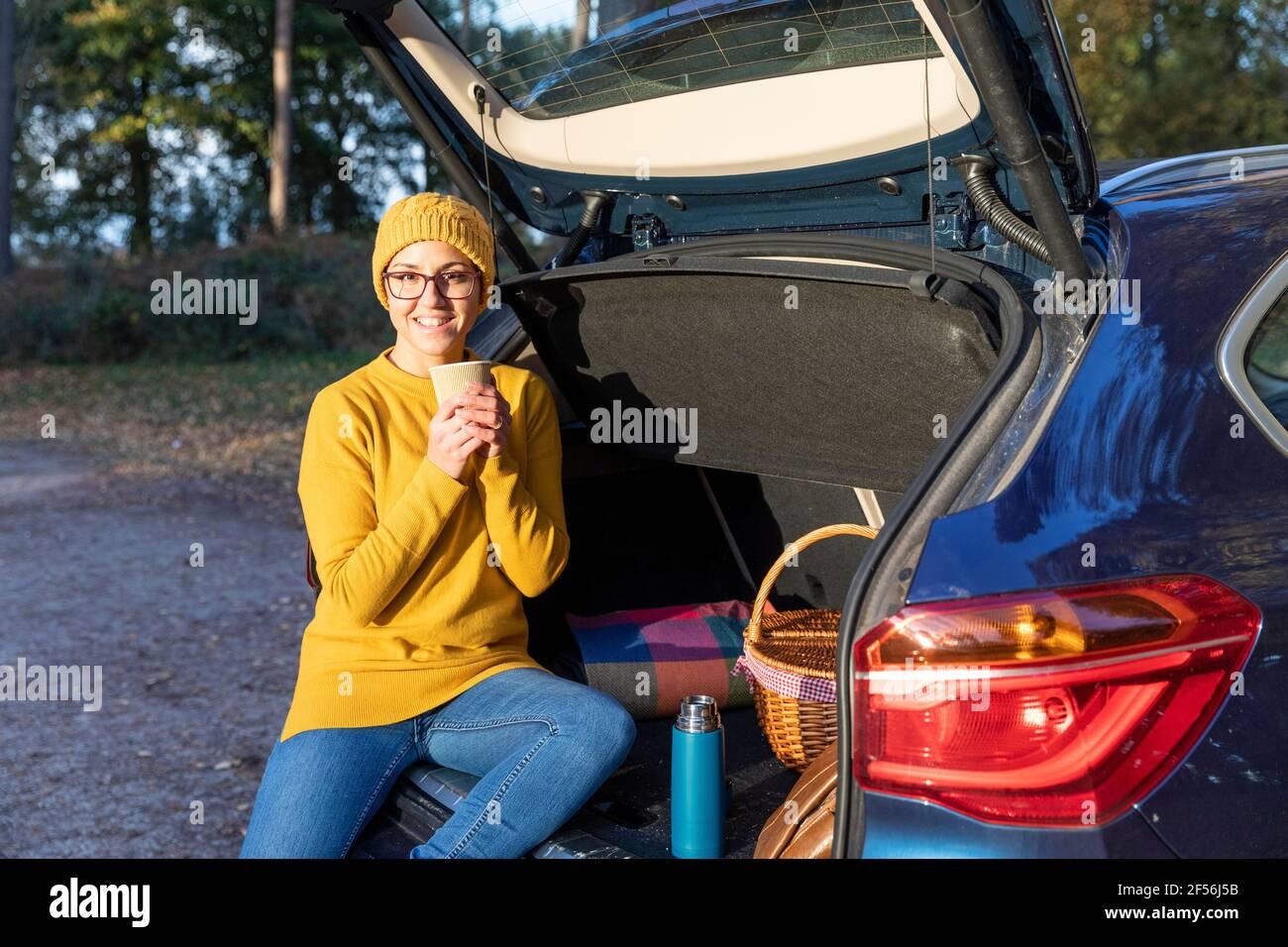 Donna sorridente che ha una bevanda calda mentre si siede nel bagagliaio dell'auto Foto Stock