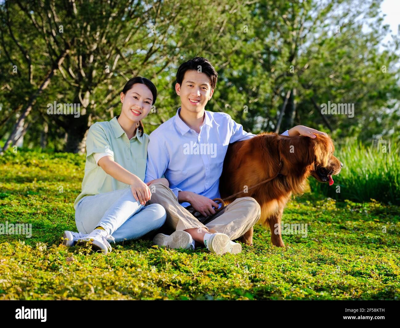 Famiglia felice di tre e cane animale domestico che gioca nel parcheggia, seduto sull'erba Foto Stock