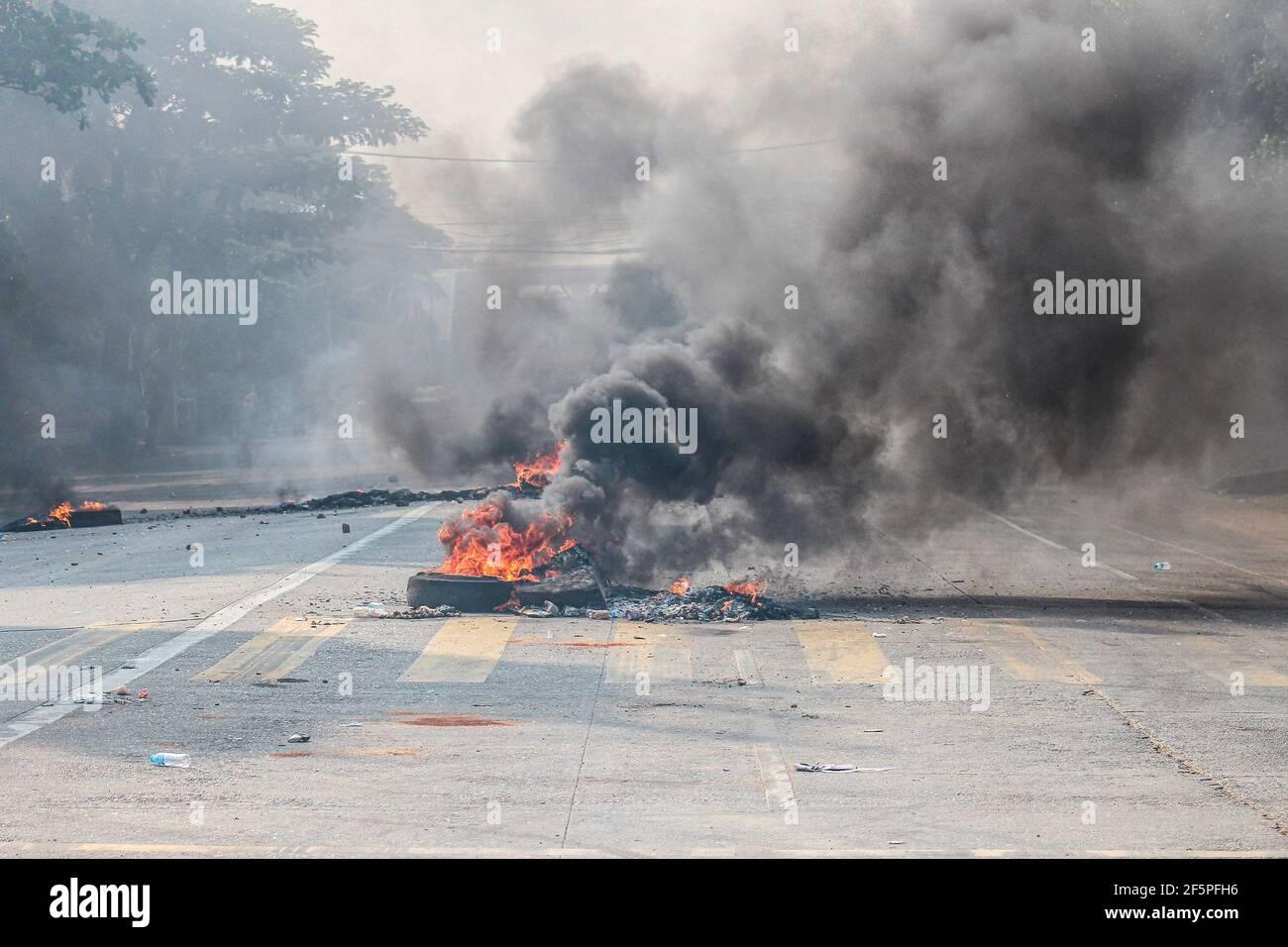 Pneumatici brucianti visti nel mezzo della strada per impedire alla polizia e ai militari di raggiungere i manifestanti antidemocratici durante una protesta contro il colpo di stato militare. La polizia e i soldati militari del Myanmar (tatmadow) hanno attaccato i dimostranti con proiettili di gomma, munizioni vive, Lacrima di gas e bombe stordite in risposta ai manifestanti anti anti-militari del colpo di stato il sabato, uccidendo più di 90 persone e ferendo molte altre. Almeno 300 persone sono state uccise in Myanmar dal colpo di Stato del 1° febbraio, ha affermato un funzionario delle Nazioni Unite per i diritti umani. Il Consigliere militare di Myanmar detenuto lo scorso febbraio da Aung San Suu Kyi Foto Stock