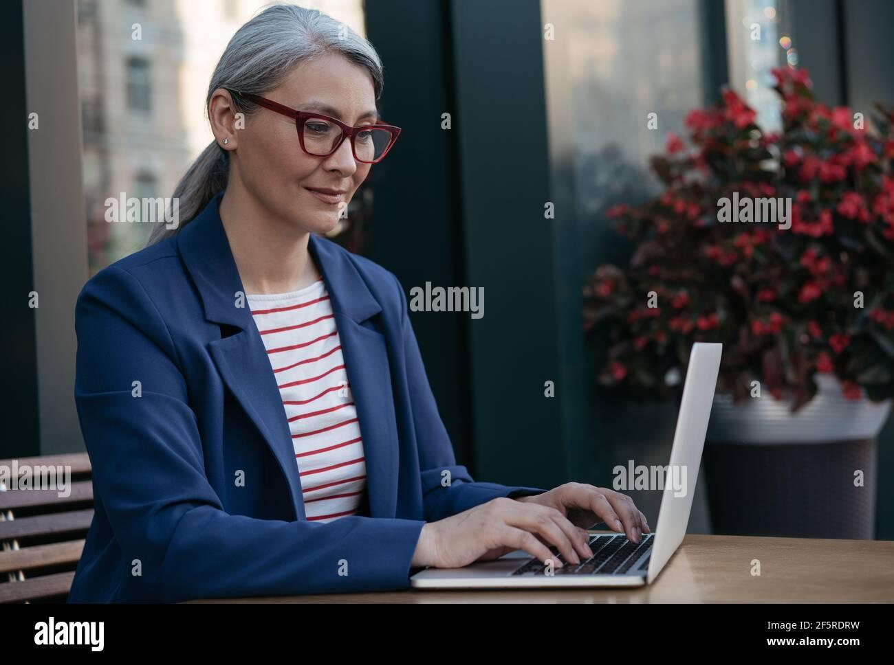 Donna d'affari matura che usa un computer portatile, che lavora online. Ritratto di copywriter asiatico di mezza età che indossa occhiali eleganti digitando sulla tastiera Foto Stock