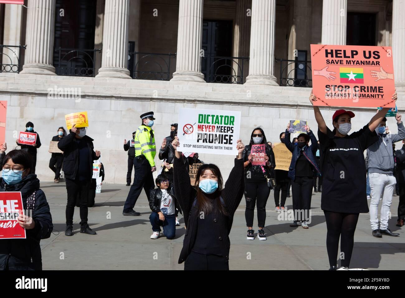 I manifestanti inginocchiano la bile che tiene cartelli esprimendo la loro opinione durante una manifestazione pacifica.Myanmar anti militari colpo di stato dimostranti riuniti a Trafalgar Square mentre dozzine di più sono uccisi nel paese. La polizia e i soldati militari del Myanmar (tatmadow) hanno attaccato i manifestanti con proiettili in gomma, munizioni vive, gas lacrimogeni e bombe stordite in risposta ai manifestanti anti anti anti militari di colpo di stato il sabato in Myanmar, uccidendo più di 90 persone e ferendo molti altri. Almeno 300 persone sono state uccise in Myanmar dal colpo di Stato del 1° febbraio, ha affermato un funzionario delle Nazioni Unite per i diritti umani. L'esercito del Myanmar ha arrestato St Foto Stock