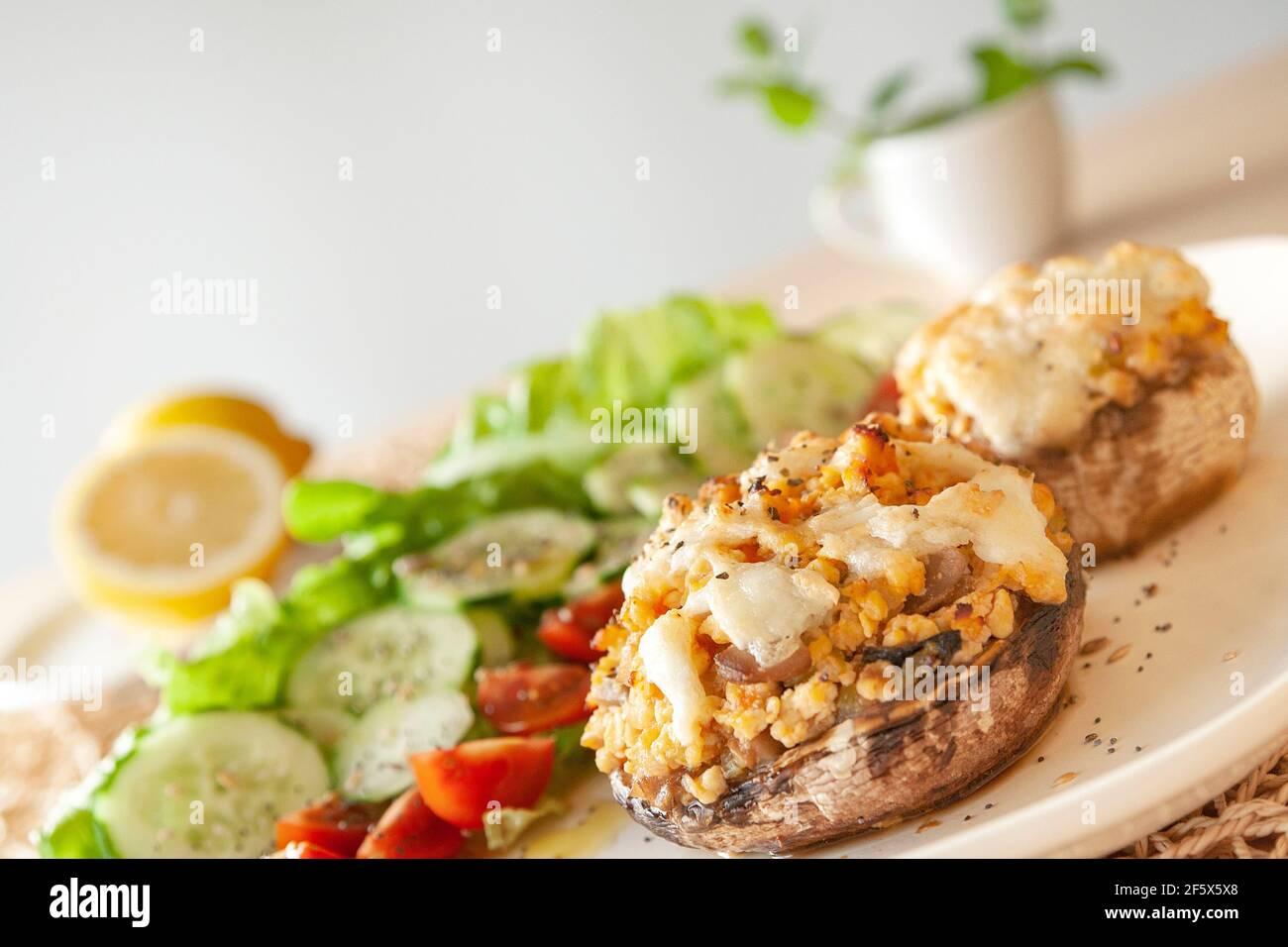 Cucina mediterranea. Funghi farciti con formaggio, insalata, pomodoro, cetriolo, limone. Foto Stock