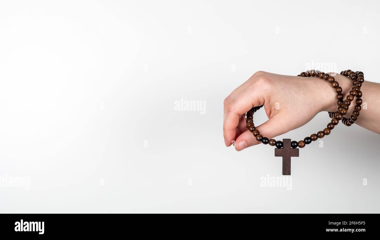 Croce di legno sulla mano della donna. Banner orizzontale con spazio per il testo, mock-up. Foto Stock