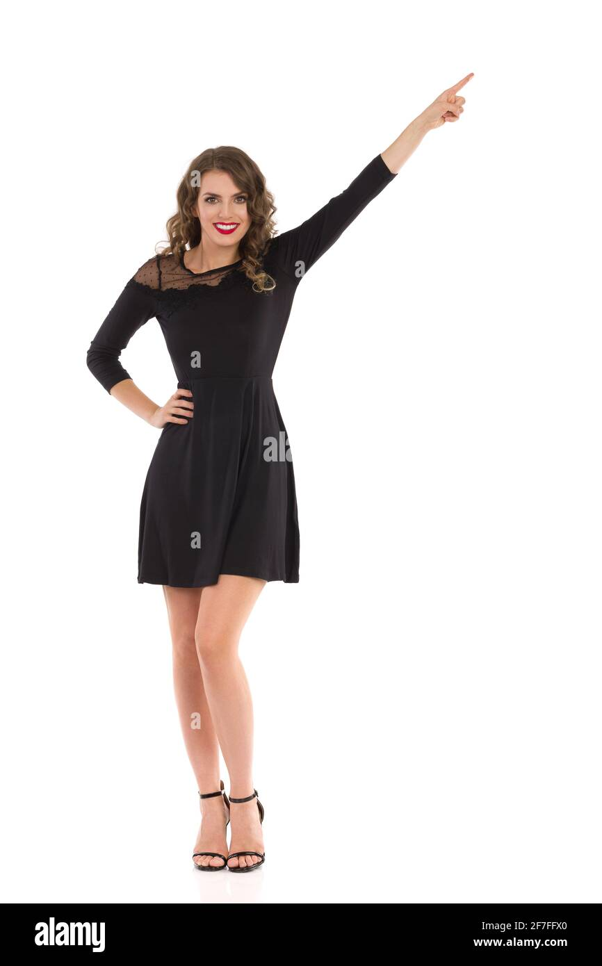 Elegante giovane donna in abito nero e tacchi alti è in piedi, puntando e sorridendo. Vista frontale. Riprese in studio a tutta lunghezza isolate su bianco. Foto Stock