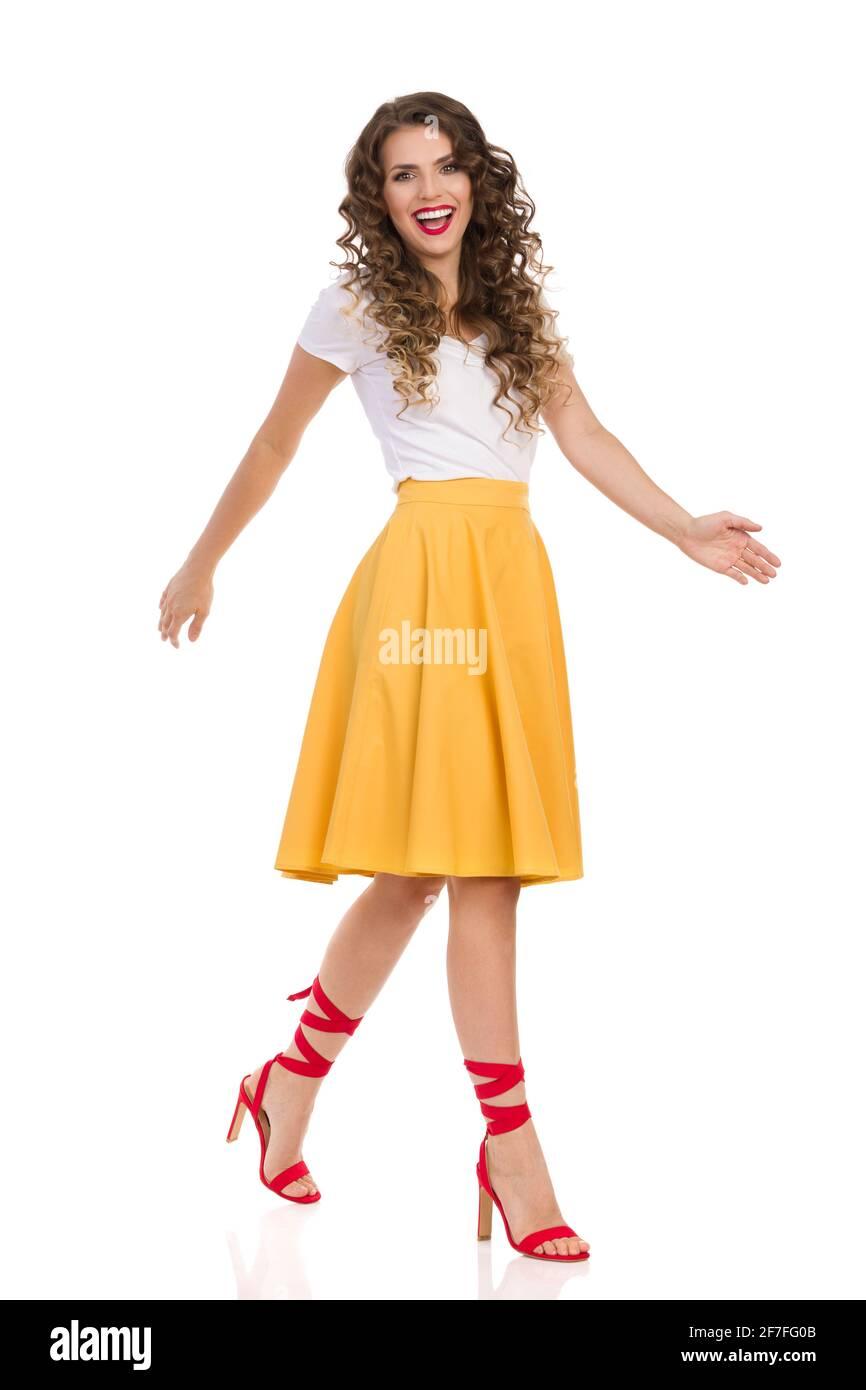 Bella giovane donna con top bianco, gonna gialla e tacchi rossi alto sta camminando e guardando camer e ridendo. Vista laterale. Foto in studio a lunghezza intera i Foto Stock
