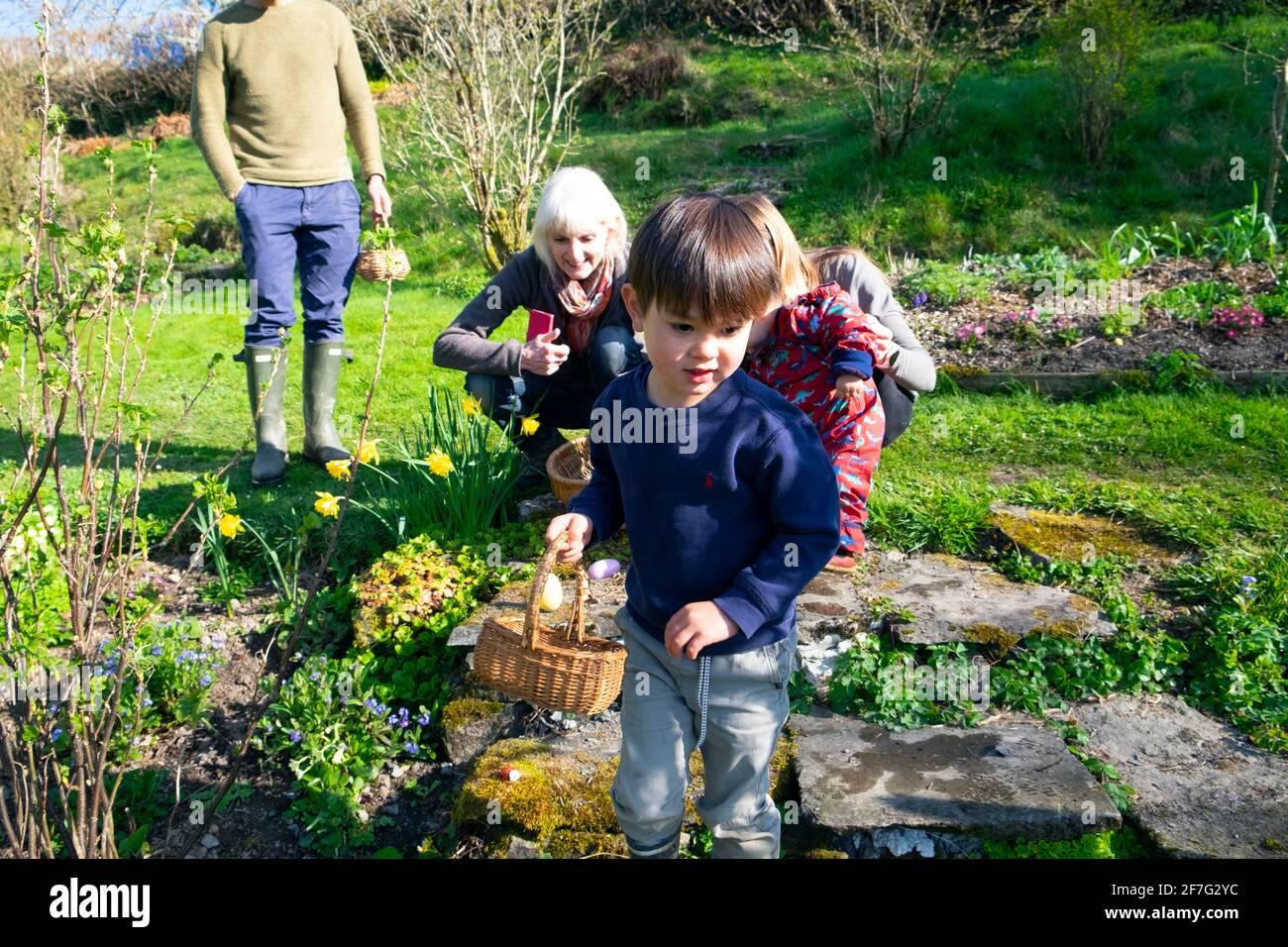 Bambino felice con i genitori e la nonna sull'uovo di Pasqua della famiglia Caccia detenere cestino caccia per uova nel giardino primaverile Galles REGNO UNITO KATHY DEWITT Foto Stock