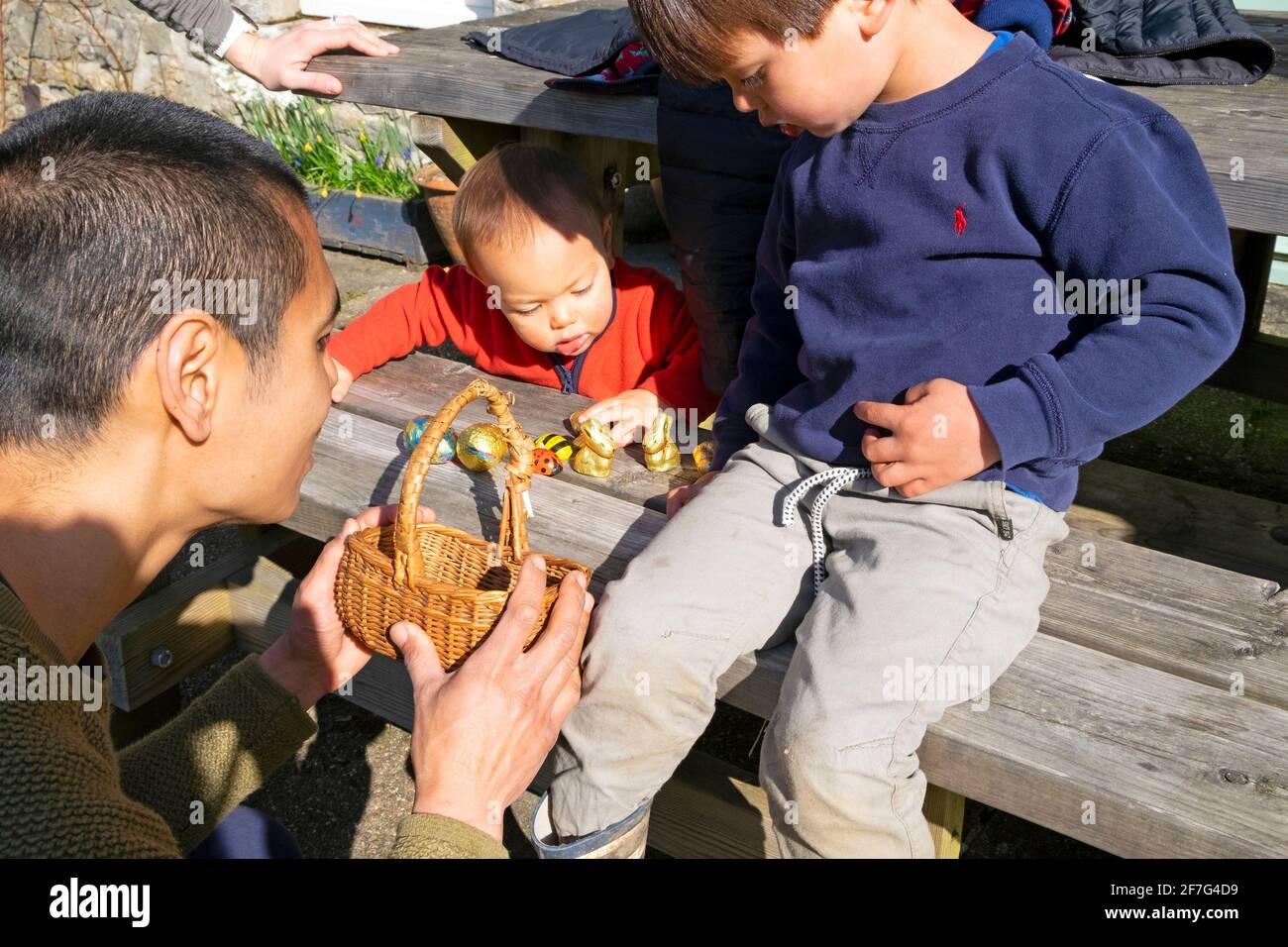 Padre asiatico con figli figli che aiutano il ragazzo 3 a contare Il suo uovo di Pasqua ha tirato dopo averli raccolti sull'uovo di Pasqua Caccia a casa in Galles Regno Unito KATHY DEWITT Foto Stock