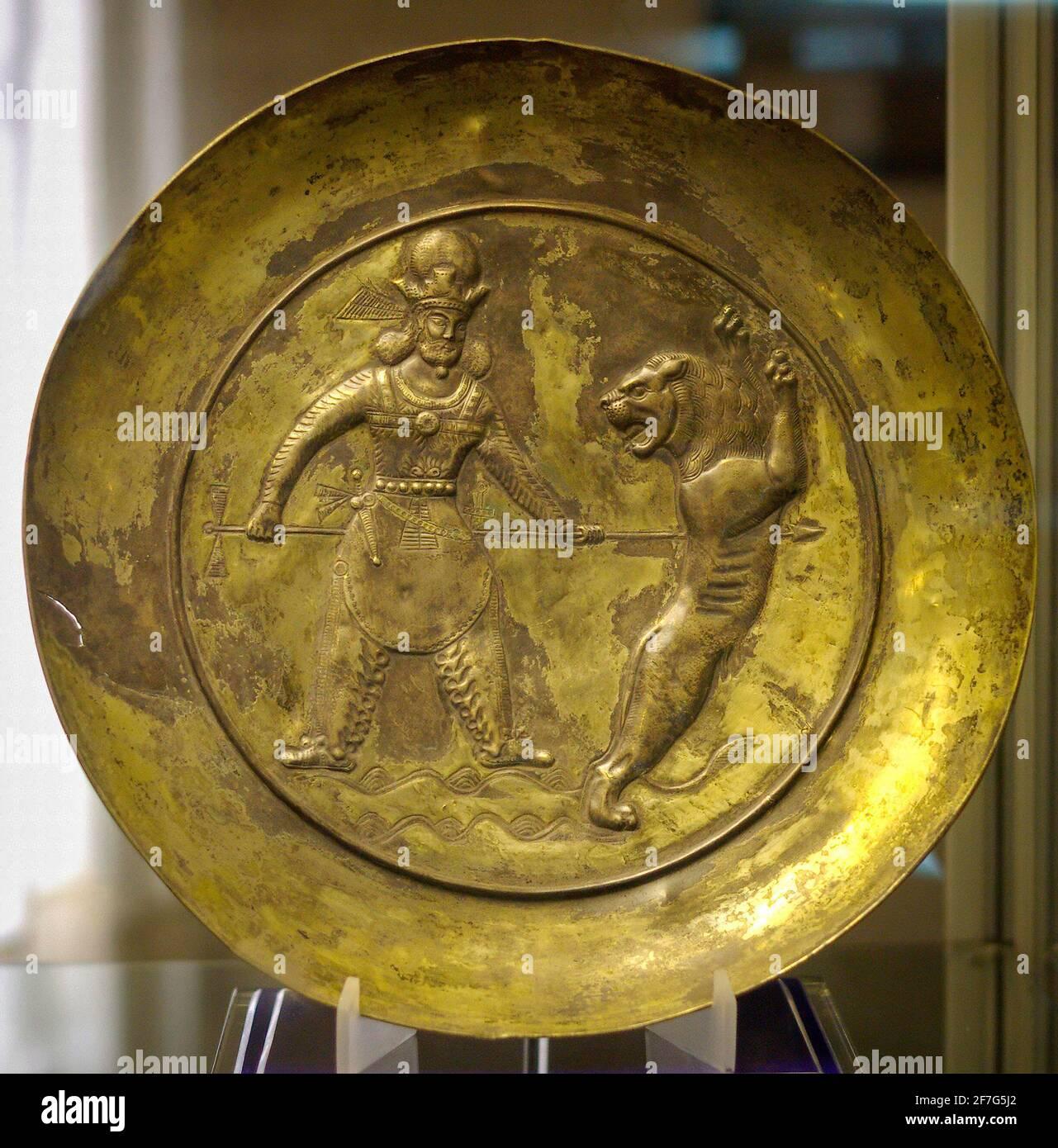 Piatto d'argento dorato sasaniano raffigurante il Re che uccide un leone con una spada, Museo Tabriz, Iran. Foto Stock
