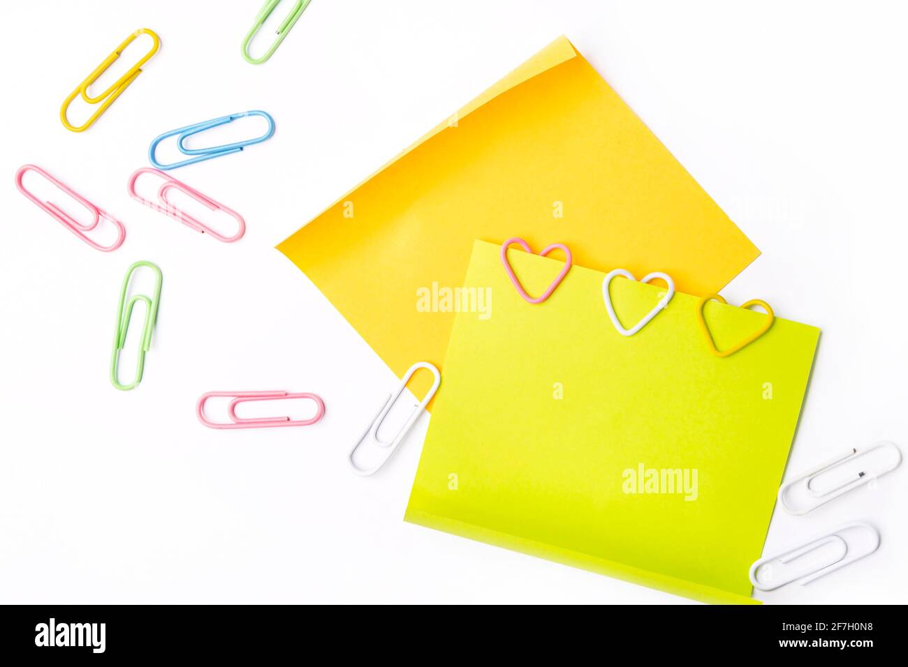Graffette a forma di cuore su note adesive fluorescenti su sfondo bianco. Foto Stock