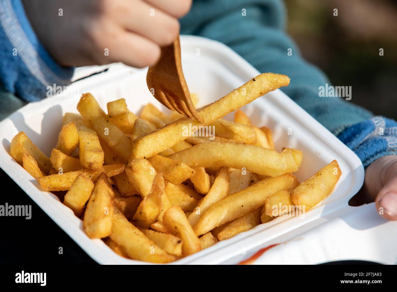 Il bambino mangia patatine fritte. Cibo malsano, da asporto e ordinazioni a casa. Foto Stock
