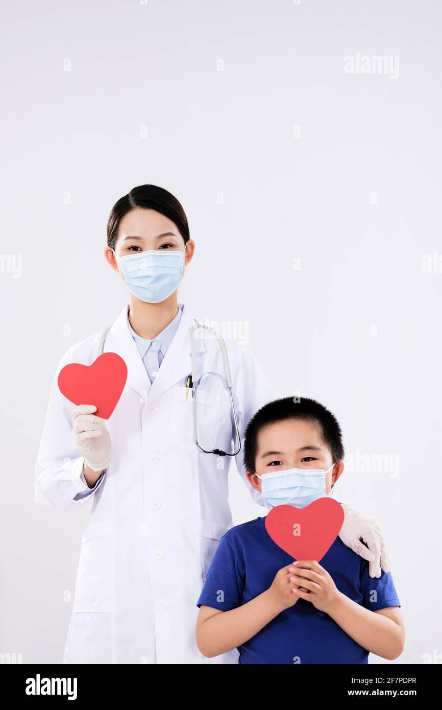 Una donna dottore e un ragazzino avevano ciascuno un cuore rosso che guarda la fotocamera Foto Stock