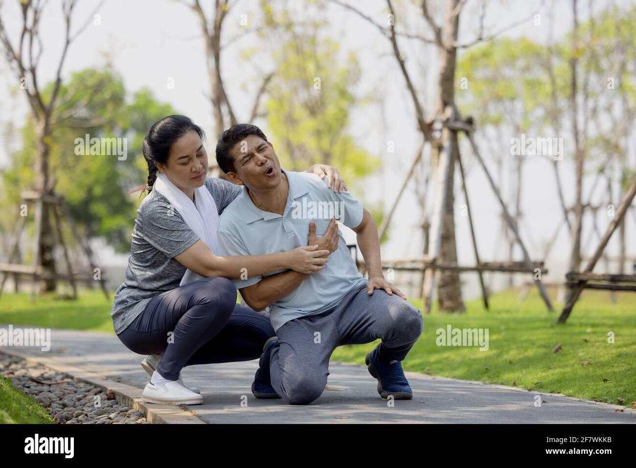 L'anziano asiatico o l'incidente dell'uomo anziano che cade sul pavimento nel parco durante l'esercizio in esecuzione hanno dolore al ginocchio. Foto Stock