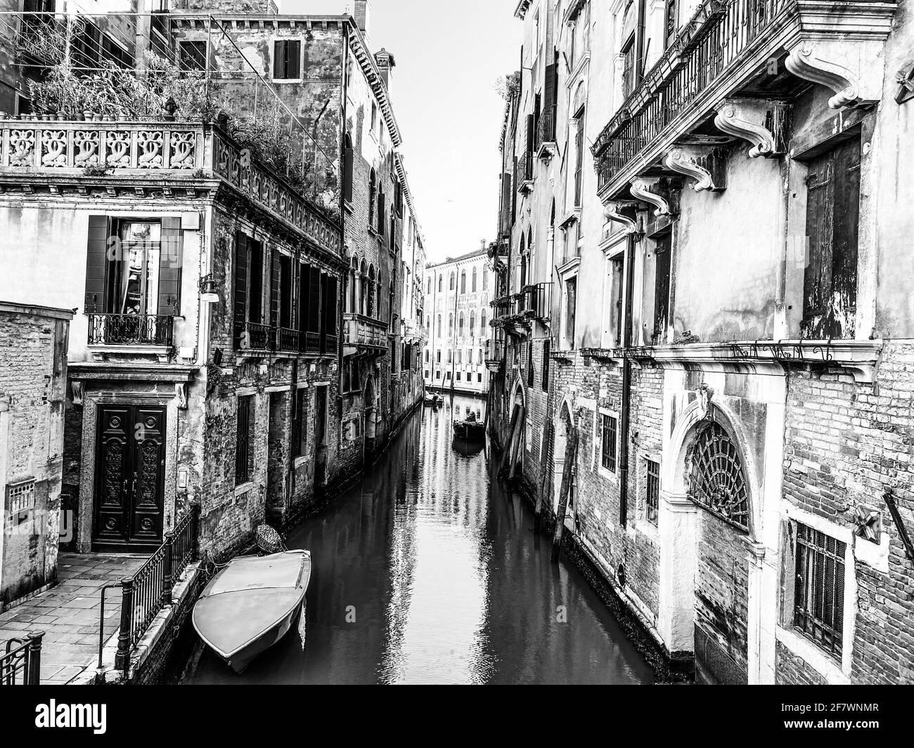 Piccola barca su una piccola strada canale a Venezia con belle case colorate, Italia Foto Stock