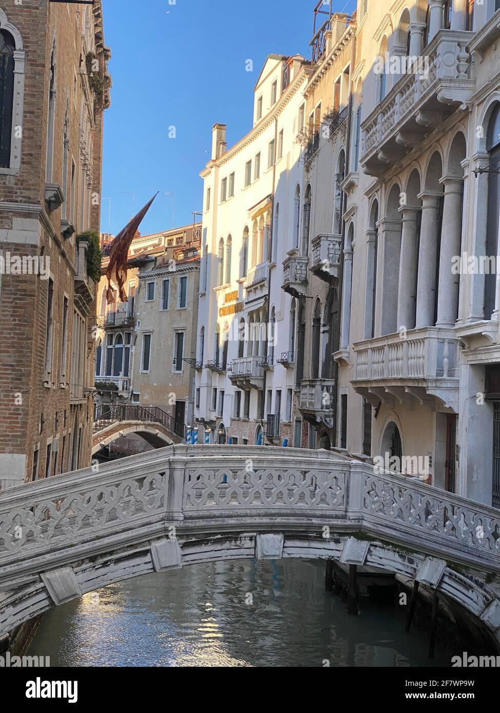 Bel ponte su un piccolo canale fiancheggiato, su sfondo colorato edificio, Venezia, Italia, durante la crisi di Lockdown COVID-19 Foto Stock