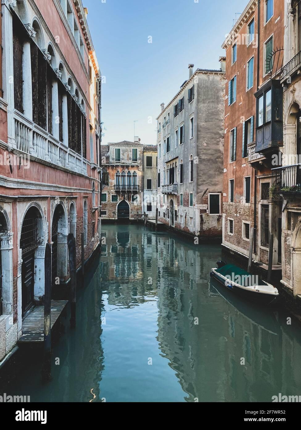 Piccola barca su una strada canale a Venezia con belle case colorate, Italia. Cielo blu Foto Stock