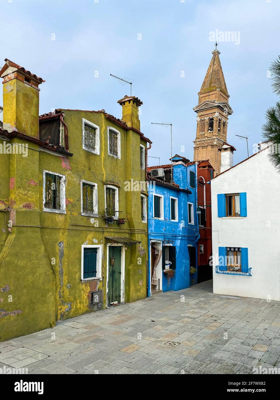 Case colorate su una piccola strada tradizionale con la cima di una chiesa che pende sull'isola di Burano, Venezia, Italia Foto Stock