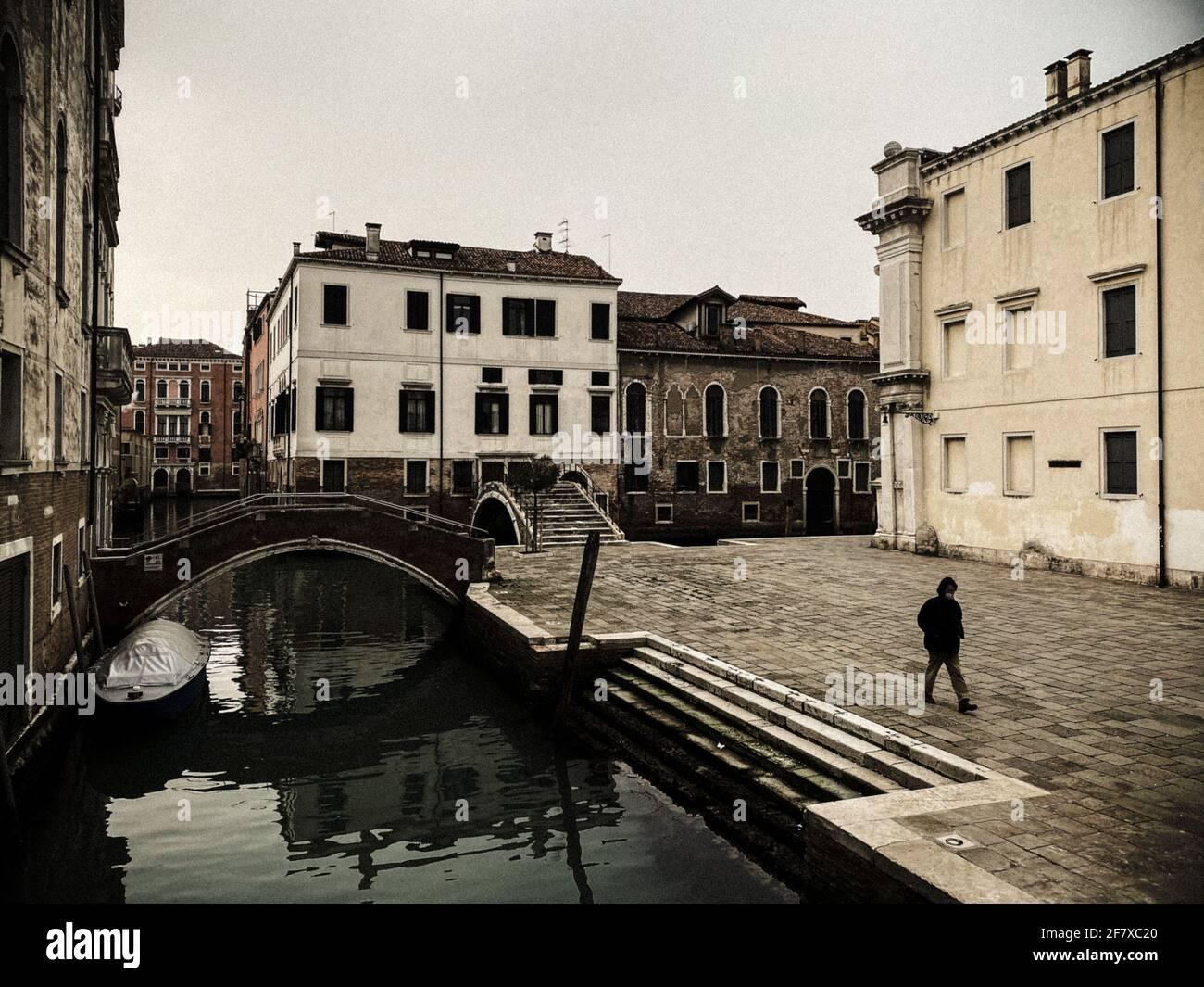 Una gente irriconoscibile che indossa una maschera che cammina in una piazza a Venezia, italia, durante la crisi COVID-19 Foto Stock