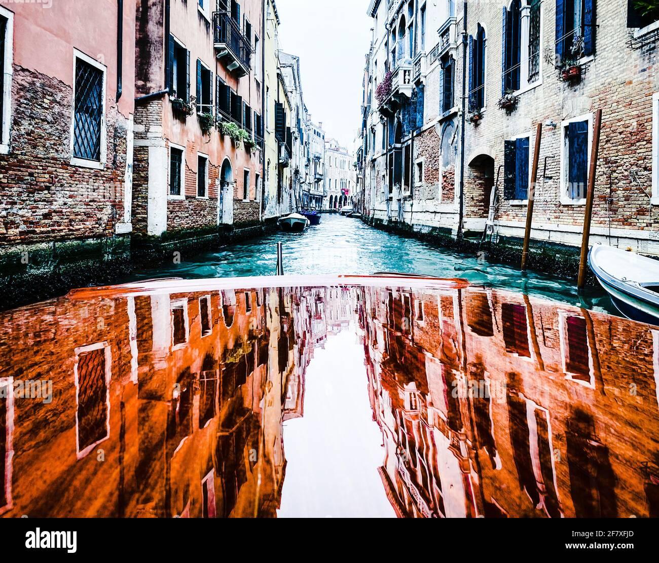 Riflessione delle case sulla cappa in legno verniciato, pontile, del taxi acqueo nelle vie di Venezia, che parte Foto Stock